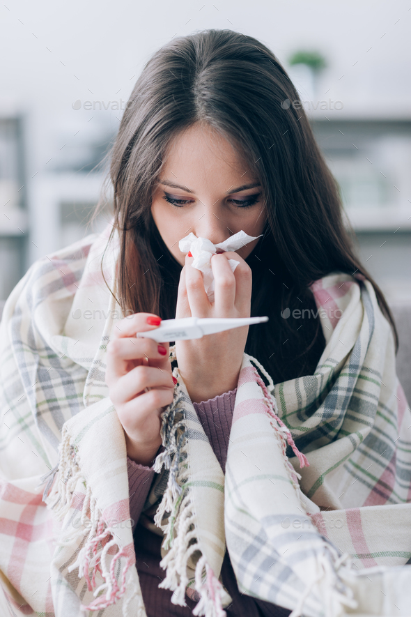 Sick woman taking temperature - Stock Photo - Images