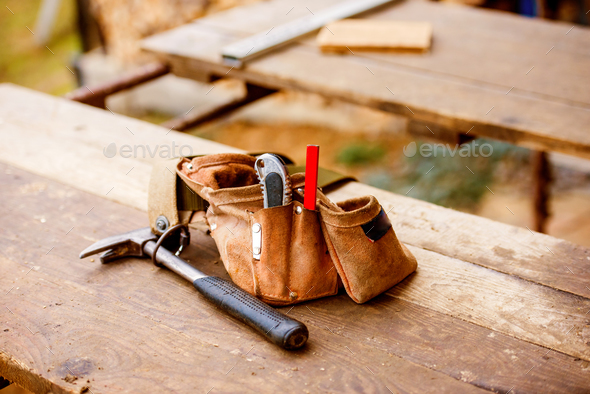 Carpenters bag with belt full of tools, wooden table - Stock Photo - Images