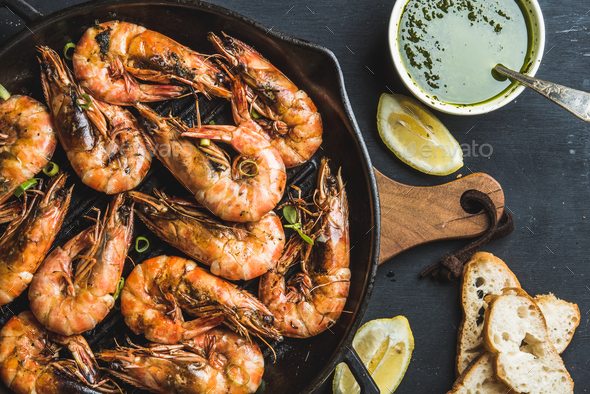 Roasted tiger prawns in iron grilling pan with fresh leek - Stock Photo - Images