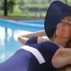 Woman Sunbathes Near The Swimming Pool - VideoHive Item for Sale