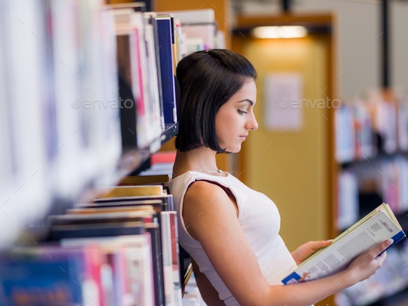 Happy female student at the library - Stock Photo - Images