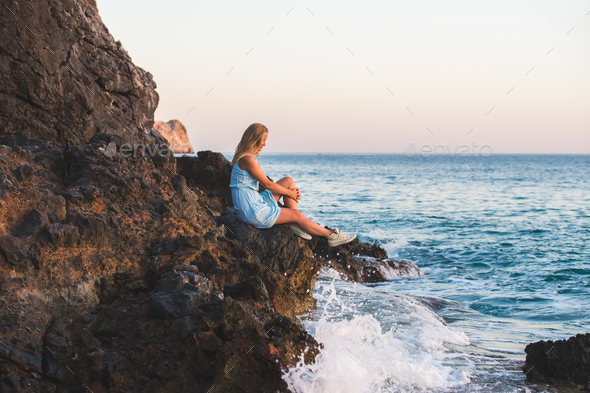Young blond woman tourist in blue dress relaxing on stone rocks - Stock Photo - Images