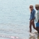 Couple Holding Hands Walking In Water On Beach - VideoHive Item for Sale