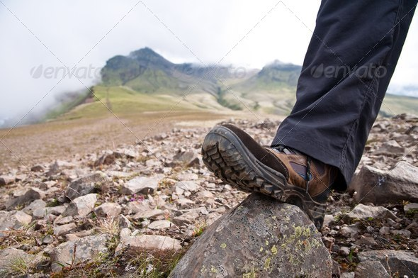 tourist in hiking shoes atop the mountain - Stock Photo - Images