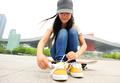 Skateboarder tying shoelace - PhotoDune Item for Sale