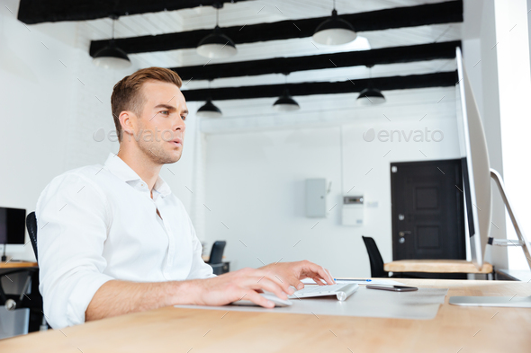 Businessman sitting and working with computer at workplace - Stock Photo - Images