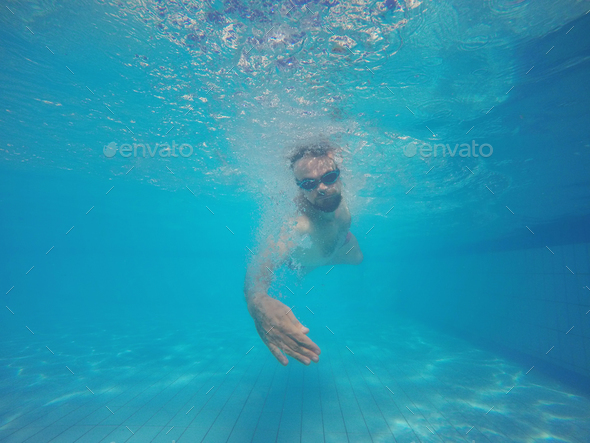 Beard man with glasses swimming under water in the pool - Stock Photo - Images