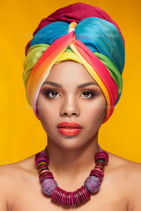 Young woman with afro american turban on yellow background - Stock Photo - Images
