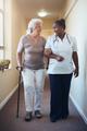 Senior woman walking being helped by female nurse - PhotoDune Item for Sale