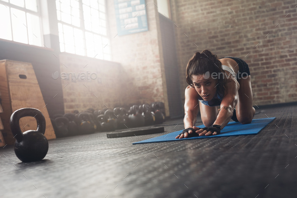 Focused woman stretching on fitness mat - Stock Photo - Images