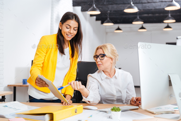 Two smiling businesswomen working together at the table in office - Stock Photo - Images