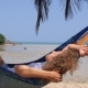 Young Woman Swinging In Hammock On Tropical Beach - VideoHive Item for Sale