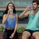 Young Sporty Couple Drinking Water, Resting After Morning Training On Bench At City - VideoHive Item for Sale