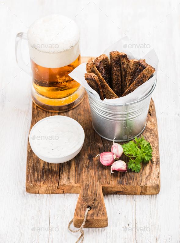 Pint of pilsener in mug, open glass bottle, rye bread croutons - Stock Photo - Images
