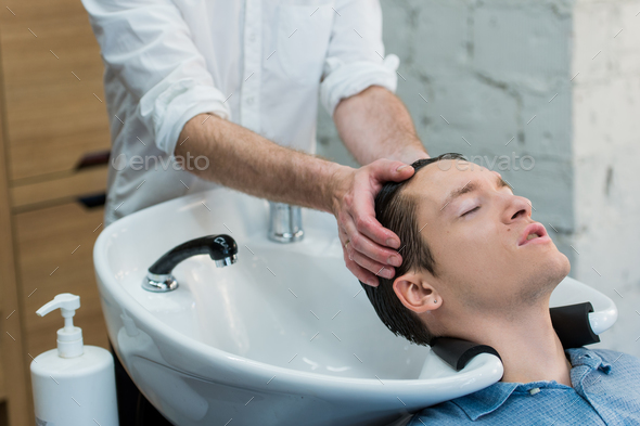Young man at hairdresser salon getting his hair washed - Stock Photo - Images