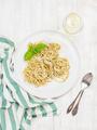 Pasta spaghetti with pesto sauce, fresh basil, glass of white