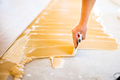 close-up of hand of worker adding glue during parquet installation - PhotoDune Item for Sale