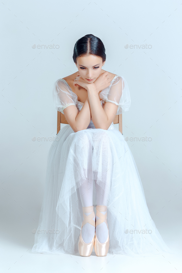 Professional ballerina sitting with her ballet shoes on the gray background - Stock Photo - Images