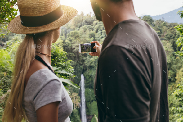 Young couple taking a picture of water fall - Stock Photo - Images