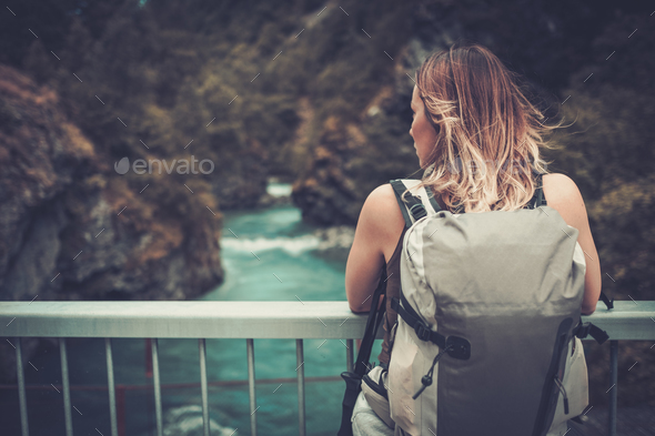 Woman hiker with backpack standing on the bridge over a wild mountain river. - Stock Photo - Images