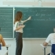 Young Teacher Near Chalkboard In School Classroom Talking To Class - VideoHive Item for Sale