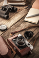 Camera with notebook and binoculars on the wooden table vertical - PhotoDune Item for Sale