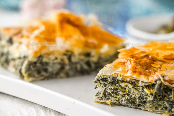 Greek pie spanakopita on the white plate with blurred accessorizes horizontal - Stock Photo - Images