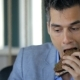 Young Man In Suit Eats Sandwich From Rye Bread And Vegetables, Drinking Tea From a Mug. - VideoHive Item for Sale