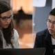 Brunette Woman In Glasses With a Young Asian Male Student With Glasses Sitting At Table, Discussing - VideoHive Item for Sale