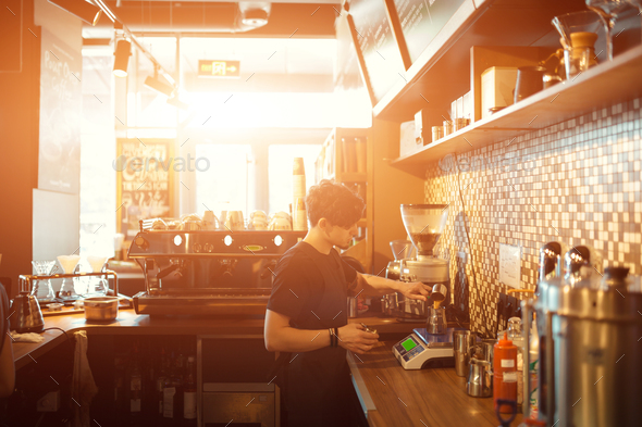 Barista at work in a coffee shop - Stock Photo - Images