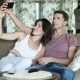 Beautiful Young Couple Is Making Selfie Using a Smart Phone And Smiling While Sitting On Sofa At - VideoHive Item for Sale