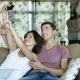 Charming Marriage Or Couple Laughing And Taking a Selfie With Phone Sitting On a Couch At Home - VideoHive Item for Sale