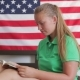 Girl Reading A Book On A Background Of The American Flag - VideoHive Item for Sale