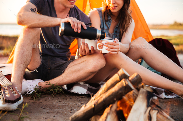 Cropped image of a couple drinking tea at the bonfire - Stock Photo - Images