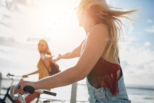 Two young female friends riding their bicycles - Stock Photo - Images