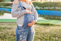 Closeup on tummy of pregnant woman outdoors, new life concept