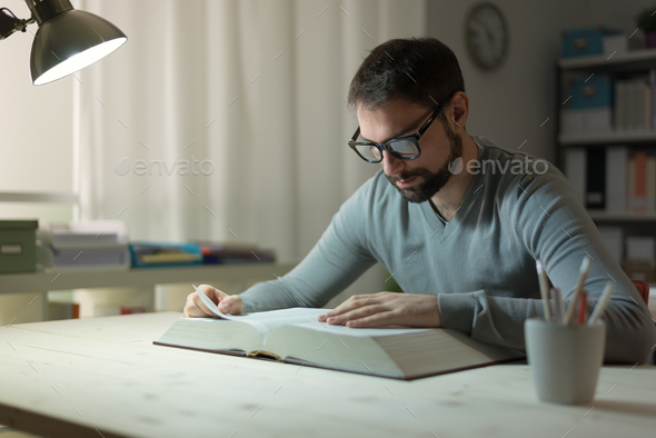 Smart man studying at night - Stock Photo - Images