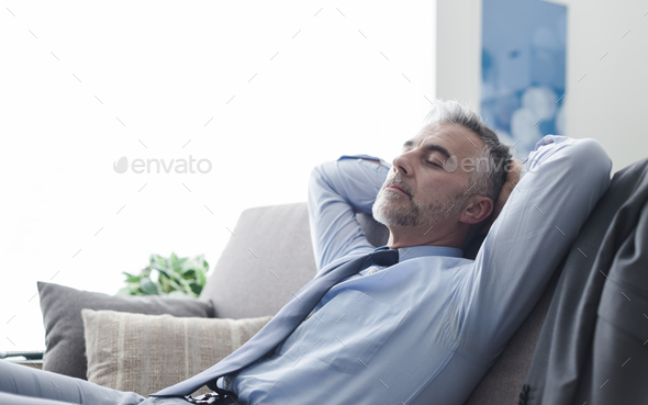 Businessman sleeping on the couch - Stock Photo - Images