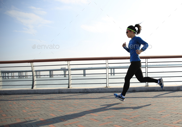 young fitness woman runner running on seaside road - Stock Photo - Images
