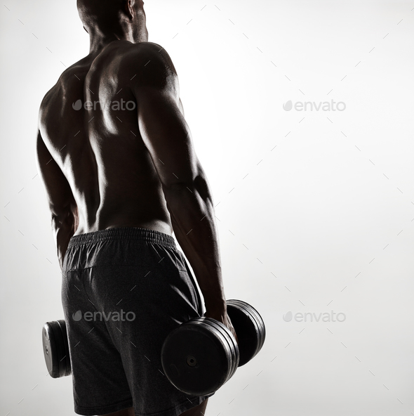 Muscular young african man exercising with dumbbells - Stock Photo - Images
