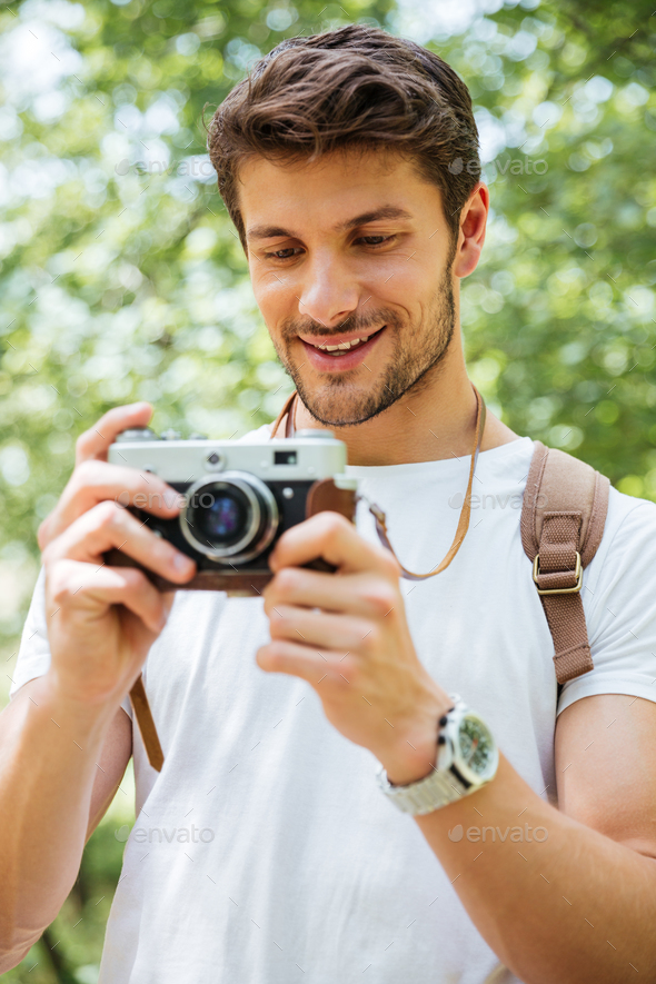 Cheerful man with backpack taking pictures using vintage camera outdoors - Stock Photo - Images