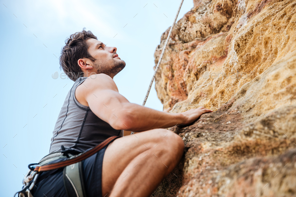 Young man climbing a steep wall in mountain - Stock Photo - Images