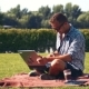 Young Smiling Man Working On Laptop In Sunny Park - VideoHive Item for Sale
