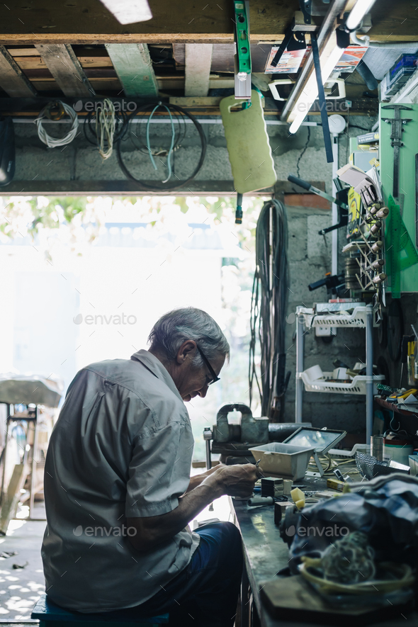 Senior mechanic working in garage - Stock Photo - Images