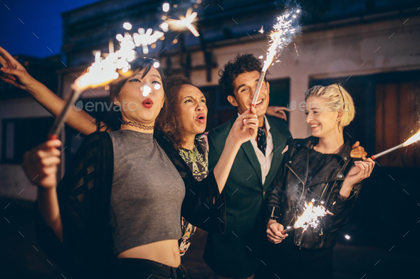Young people enjoying new years eve with fireworks - Stock Photo - Images