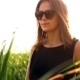 Girl Black Sunglasses Goes Across The Field Through Tall Grass Portrait - VideoHive Item for Sale