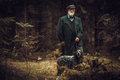 Senior man with dog in a traditional shooting clothing, posing on a dark forest background. - PhotoDune Item for Sale