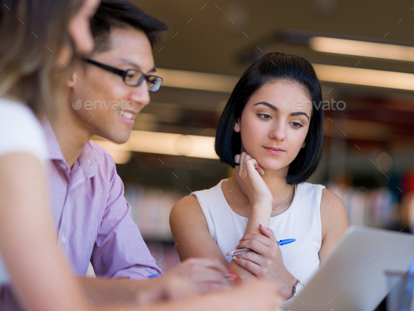 Group of young students at the library - Stock Photo - Images