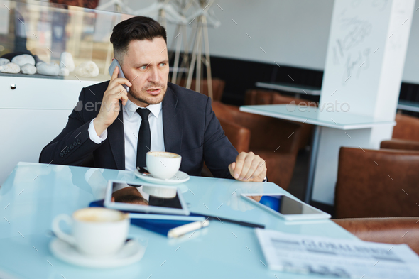 Businessman calling in cafe - Stock Photo - Images