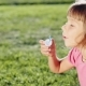Cute Little Girl Is Blowing Soap Bubbles In The Garden Outdoors On a Sunny Day - VideoHive Item for Sale